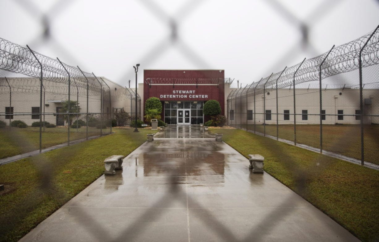 The Stewart Detention Center is seen through the front gate, Friday, Nov. 15, 2019, in Lumpkin, Ga. The rural town is about 140 miles southwest of Atlanta and next to the Georgia-Alabama state line. The town's 1,172 residents are outnumbered by the roughly 1,650 male detainees that U.S. Immigration and Customs Enforcement said were being held in the detention center in late November.