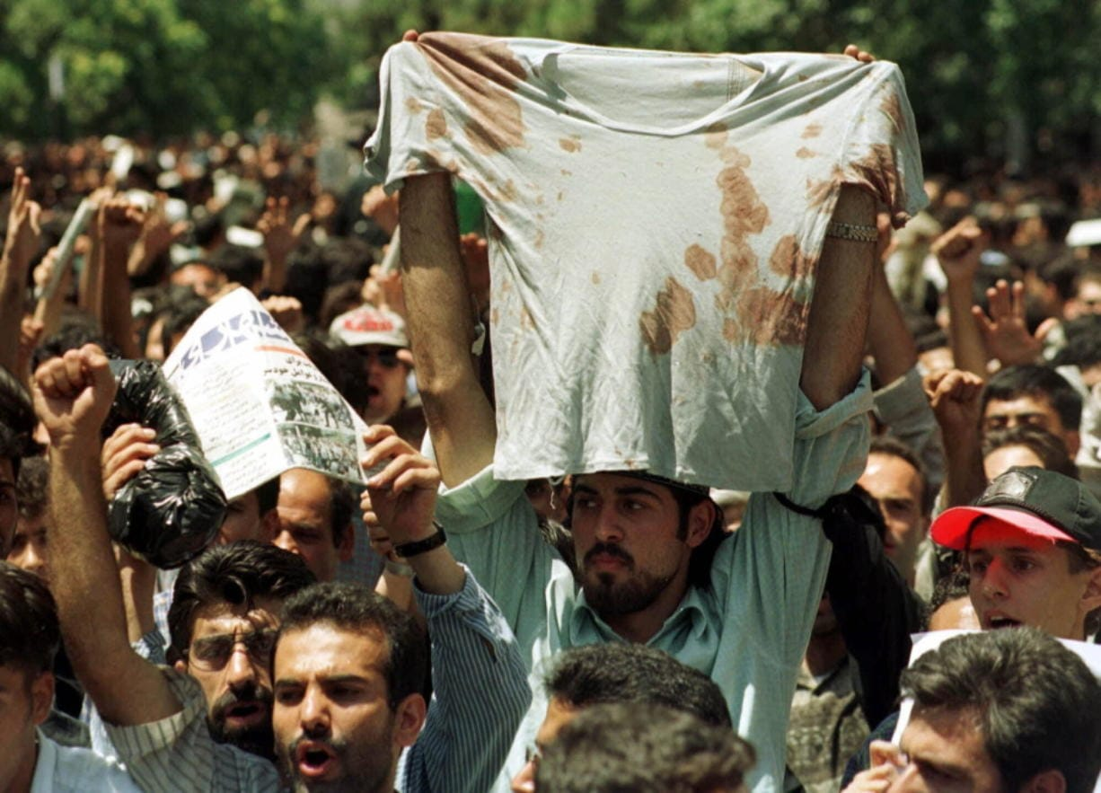 FILE - In this July 12, 1999 file photo, an unidentified student at a rally in Tehran, Iran, holds up the bloody t-shirt of a friend who was injured sometime in the last few days during clashes between police and student demonstrators. The demonstrations that erupted after Iran admitted to accidentally shooting down a Ukrainian jetliner early Wednesday, Jan. 8, 2020, during a tense standoff with the United States, are the latest of several waves of protest going back to the 1979 Islamic Revolution -- all of which have been violently suppressed. (AP Photo/Kamran Jebreili, File)