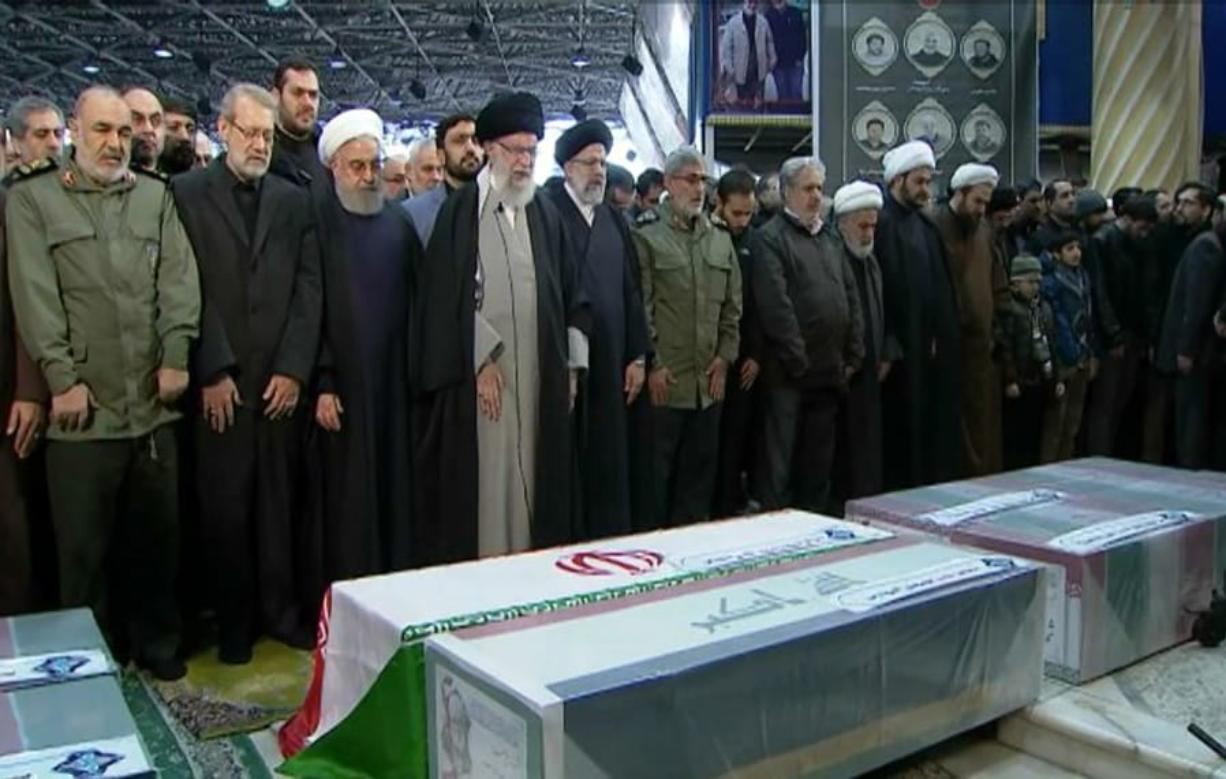 FILE- In this photo released by the official website of the Office of the Iranian Supreme Leader, supreme leader Ayatollah Ali Khamenei, front row, fourth from left, leads a prayer over the coffins of Gen. Qassem Soleimani and his comrades, who were killed in Iraq in a U.S. drone strike on Friday, at the Tehran University campus, in Tehran, Iran, Monday, Jan. 6, 2020.