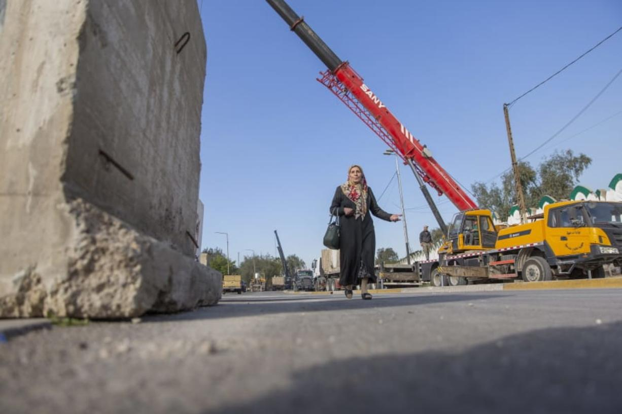 A woman passes by Iraqi security forces while they remove cement blocks and open the streets, that were closed for security concerns, around the Green Zone in Baghdad, Iraq, Thursday, Jan. 2, 2020. Iran-backed militiamen have withdrawn from the U.S. Embassy compound in Baghdad after two days of clashes with U.S. security forces. (AP Photo/Nasser Nasser)