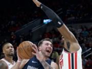 Dallas Mavericks guard Luka Doncic (77) drives to the basket past Portland Trail Blazers center Hassan Whiteside during the first half of an NBA basketball game in Portland, Ore., Thursday, Jan. 23, 2020.