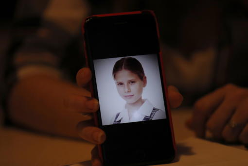 In this Jan. 14, 2020 photo, Ana Lucia Salazar shows a photo of herself when she was 8-years-old, on her smart phone during an interview with the Associated Press in Mexico City. At the time Salazar says she was sexually abused by a Legion of Christ priest. (AP Photo/Marco Ugarte)