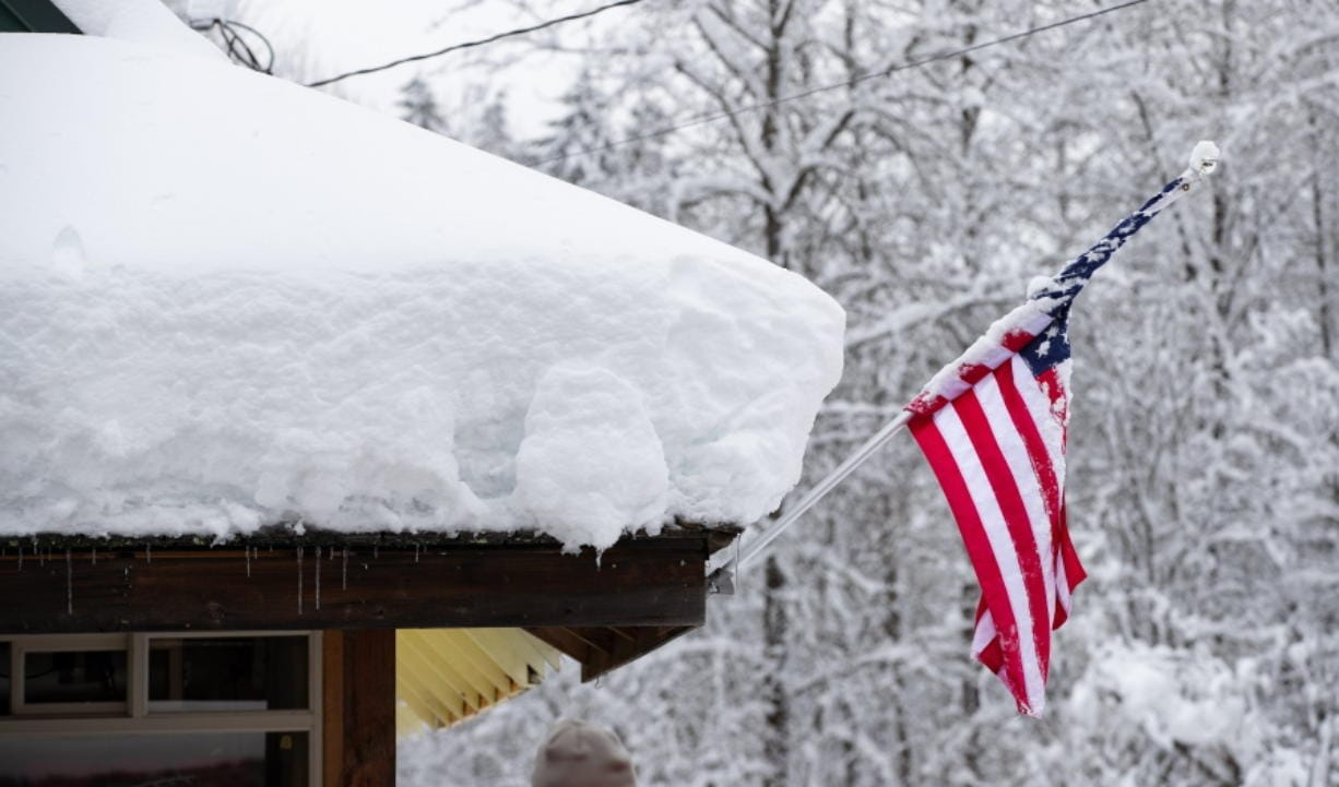 Snow covers the roof of Steven's Pizza in Skykomish, Wash., along Highway 2, Wednesday, Jan. 15, 2020, in Skykomish, Wash. Volunteers brought food and supplies here for local Skykomish residents stranded without power or access to food.