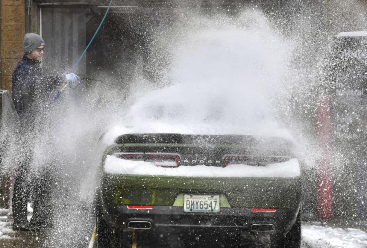 Vehicles maneuver down slick slick road packed hard with snow Tuesday, Jan. 14, 2020, in Edmonds, Wash. (Steve Ringman/The Seattle Times via AP)