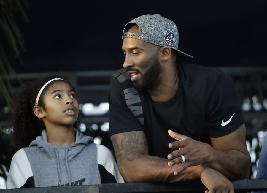 FILE - In this July 26, 2018 file photo former Los Angeles Laker Kobe Bryant and his daughter Gianna watch the U.S. national championships swimming meet in Irvine, Calif. Bryant, the 18-time NBA All-Star who won five championships and became one of the greatest basketball players of his generation during a 20-year career with the Los Angeles Lakers, died in a helicopter crash Sunday, Jan. 26, 2020. Gianna also died in the crash.