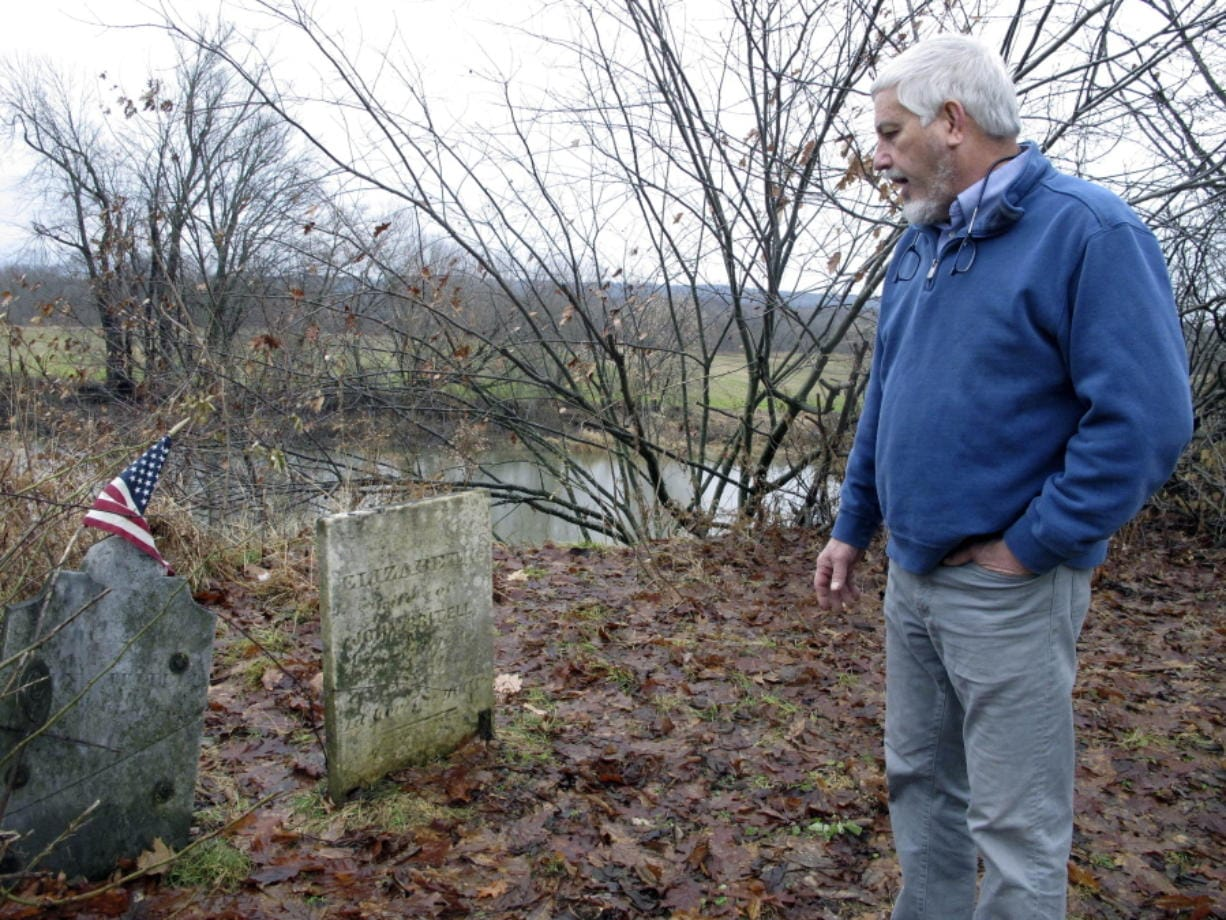 In this Dec. 10, 2019, photo, Don Mason, chairman of the Weybridge, Vt., selectboard looks at gravestone of Revolutionary War soldier William Haven, who is buried in a cemetery near the edge of an eroding river bank in Weybridge, Vt. Rising seas, erosion and flooding from worsening storms that some scientists believe are caused by climate change are putting some older graveyards across the country at risk.