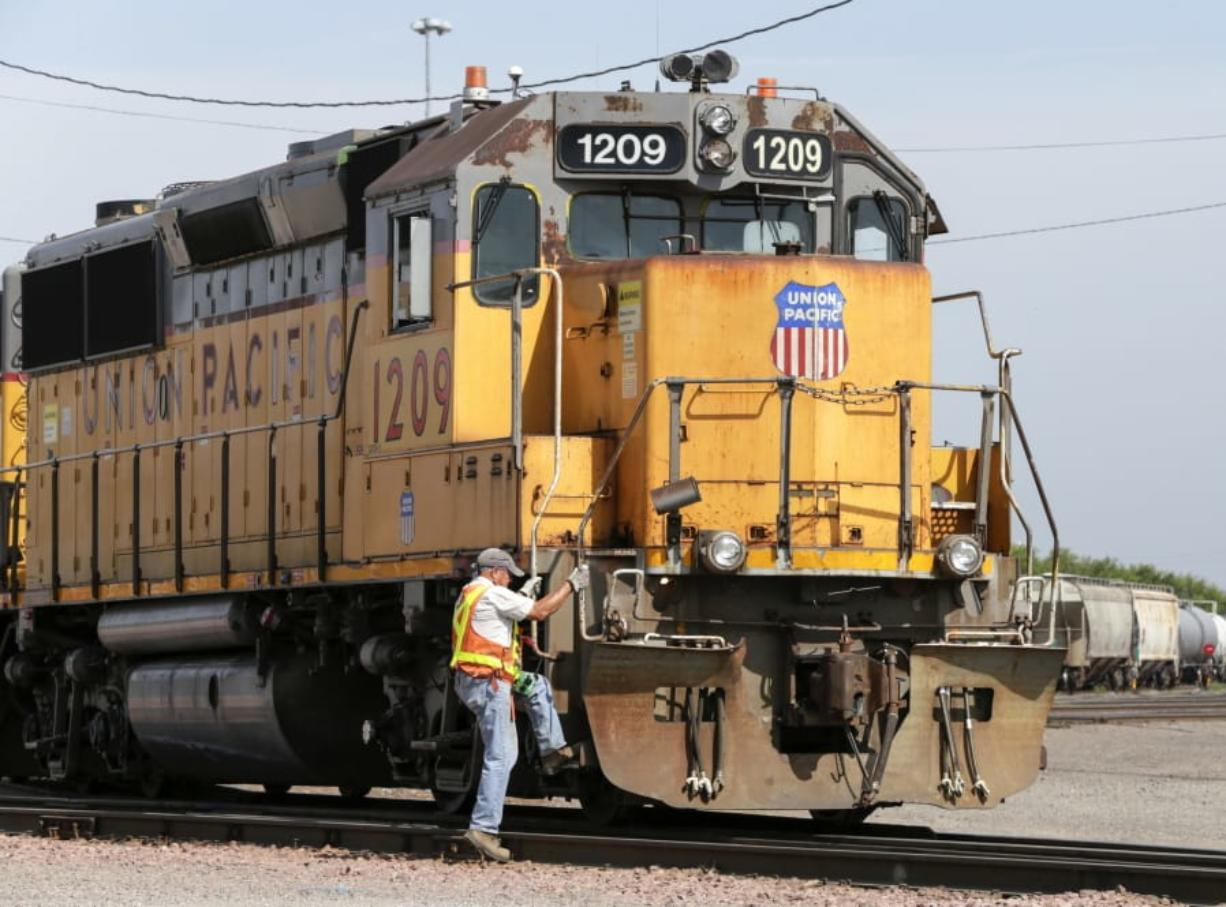 FILE - In this July 20, 2017, file photo, a Union Pacific employee climbs on board a locomotive in a rail yard in Council Bluffs, Iowa. This year's scheduled completion of a $15 billion automatic railroad braking system will bolster the industry's argument for eliminating one of the two crew members in most locomotives. But labor groups argue that single-person crews would make trains more accident prone.