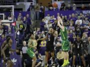 Oregon guard Payton Pritchard, right, shoots the game-winning 3-point basket as Washington guard Jamal Bey (5) tries for the block during overtime in an NCAA college basketball game, Saturday, Jan. 18, 2020, in Seattle. Oregon won 64-61 in overtime. (AP Photo/Ted S.