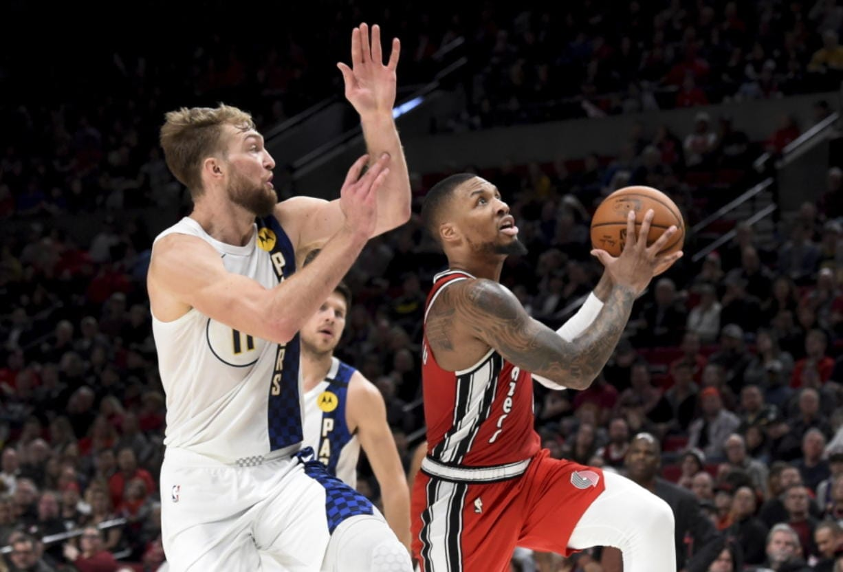 Portland Trail Blazers guard Damian Lillard, right, drives to the basket on Indiana Pacers forward Domantas Sabonis, left, during the second half of an NBA basketball game in Portland, Ore., Sunday, Jan. 26, 2020. Lillard scored 50 points as the Blazers won 139-129.