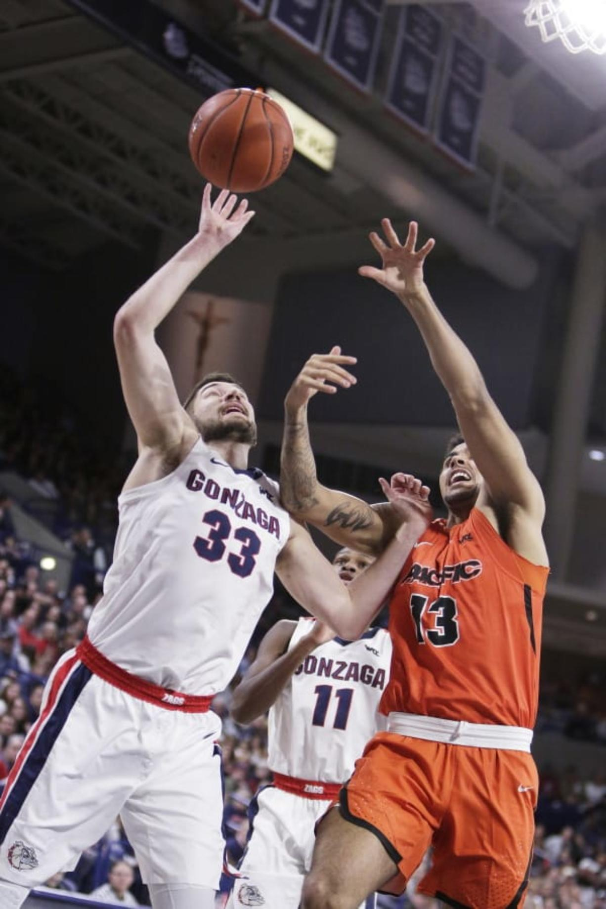 Gonzaga forward Killian Tillie (33) and Pacific forward Jeremiah Bailey (13) go after a rebound during the first half of an NCAA college basketball game in Spokane, Wash., Saturday, Jan. 25, 2020.