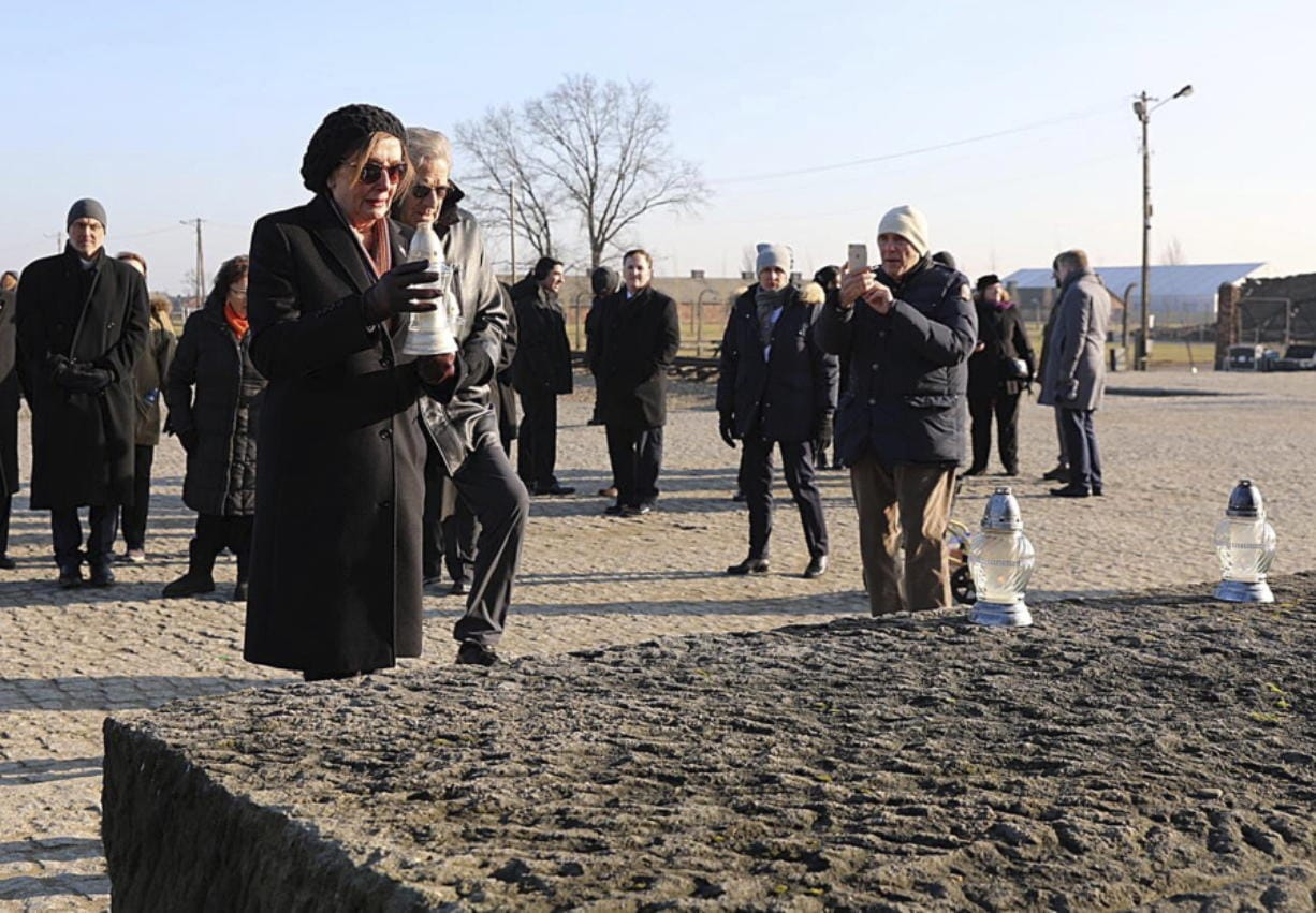In this image provided by the US Consulate General in Krakow, U.S. House Speaker Nancy Pelosi places a memorial light on the monument to some 1.1 million victims of the World War II Nazi death camp of Auschwitz-Birkenau during a visit to the site of the former camp just days before the 75th anniversary of its 1945 liberation by the Soviet troops, at the Auschwitz-Birkenau Museum, in southern Poland, on Tuesday, Jan. 21, 2020.