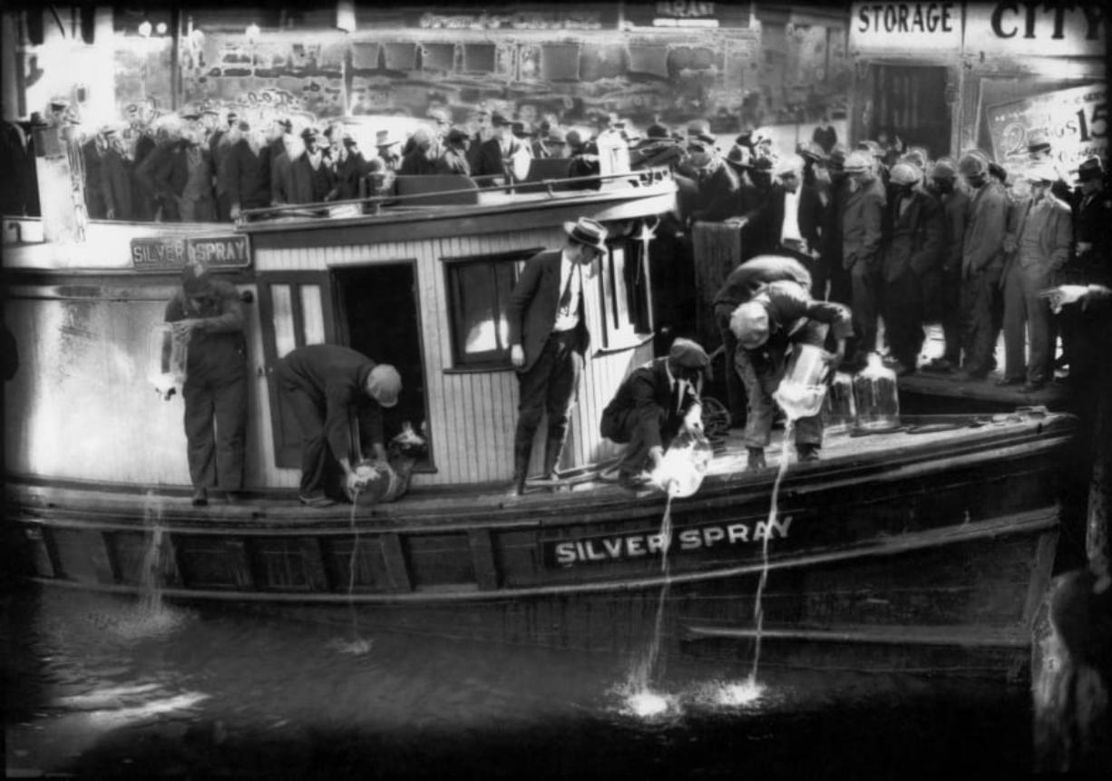 """FILE - In this 1922 file photo spectators gather by the side of captured rum runner, Silver Spray, as they watch prohibition agents pour """"white lightning"""" from the five-gallon bottles on the deck into the Elizabeth River, Norfolk, Va. The Prohibition Era, which lasted from Jan. 17, 1920, until December 1933, is now viewed as a failed experiment that glamorized illegal drinking. (Charles S. Borjes/The Virginian-Pilot via AP)"""