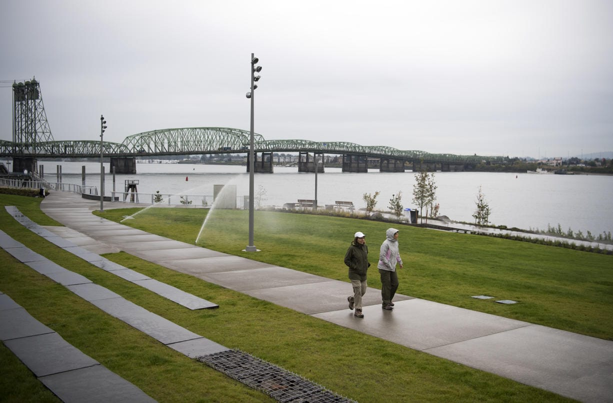 """Kim Pohlman of Vancouver, left, Karen Conway of Cincinnati, Ohio, right, and walk along the Vancouver Waterfront Park on Friday afternoon, Oct. 5, 2018. Conway use to live in Vancouver and is back for a visit so the friends decided to brave the rain to check it out. """"We were smiling because rain doesn't stop us,"""" Pohlman said.    (Alisha Jucevic/The Columbian)"""