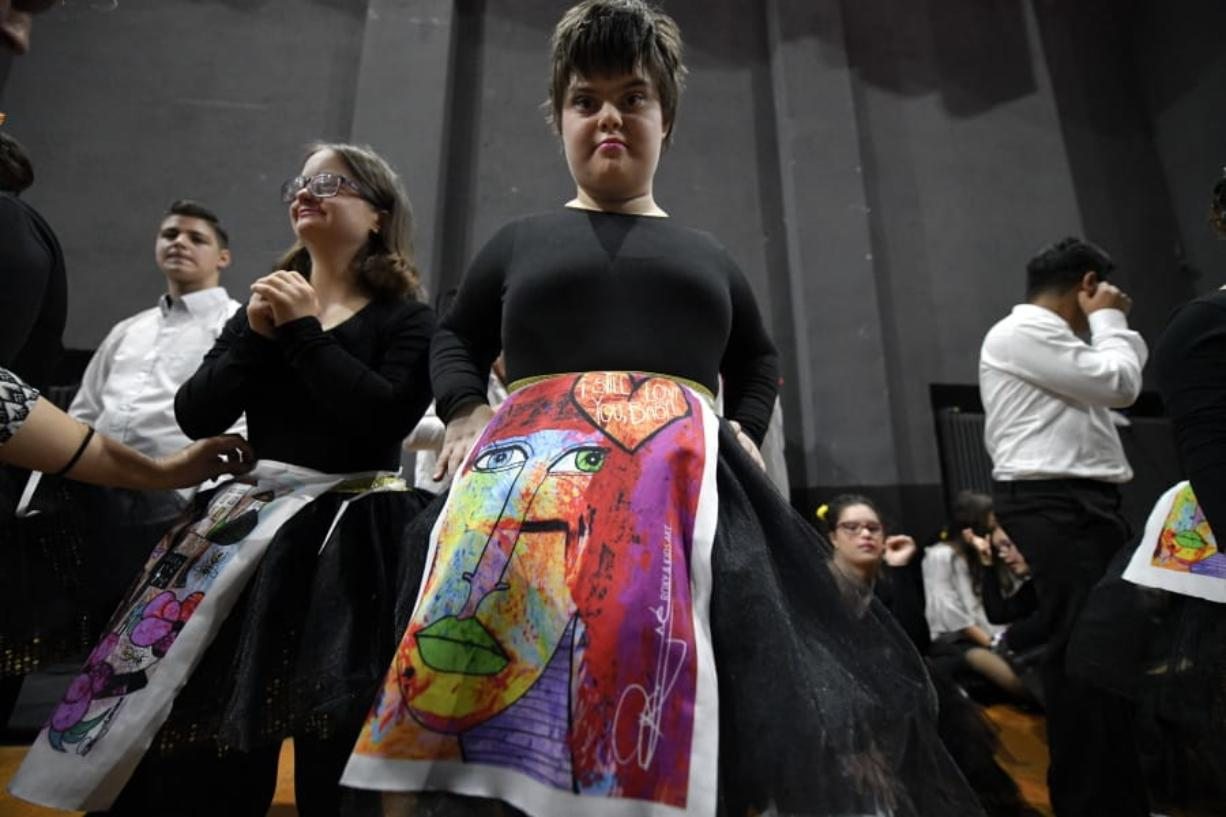"In this Nov. 3, 2019, photograph a child with Down syndrome prepare to show skirts displaying drawings inspired by children, during a fashion show dubbed ""heART Couture"" in Bucharest, Romania. Children with Down syndrome staged a fashion show and performed along a ballet ensemble, two milestone events for the inclusion of people with disabilities in Romania's social life, 30 years after the fall of communism following a violent uprising at the end of 1989.(AP Photo/Andreea Alexandru)"