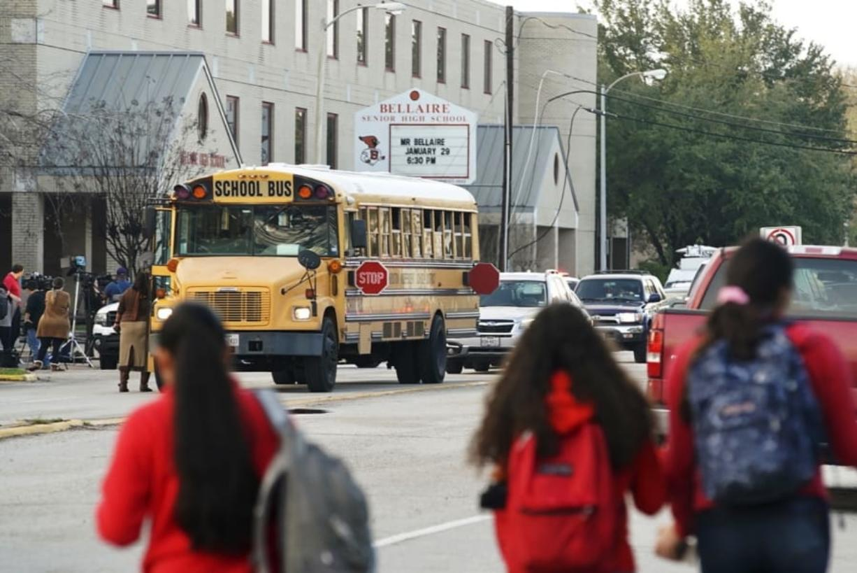 Students watch from across the street as authorities respond to a shooting at Bellaire High School in Bellaire, Texas, Tuesday, Jan. 14, 2020.