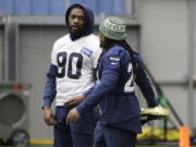 Seattle Seahawks running back Marshawn Lynch, right, stretches as he talks with defensive end Jadeveon Clowney, left, before NFL football practice, Friday, Dec. 27, 2019, in Renton, Wash. (AP Photo/Ted S.