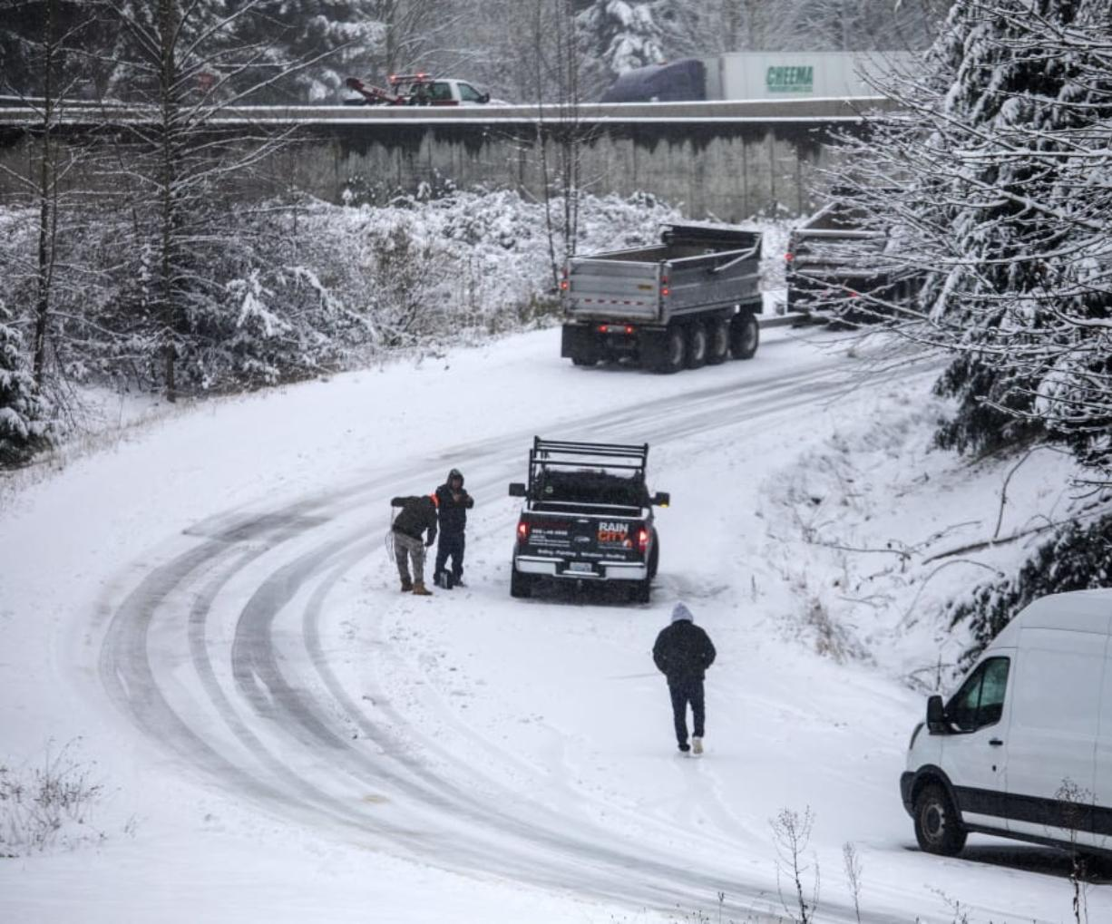 A driver starts to put on chains in compact snow and ice on the NE 72nd Place on-ramp to Highway 405 in Kirkland, Wash., Monday, Jan. 13, 2020. (Steve Ringman/The Seattle Times via AP)