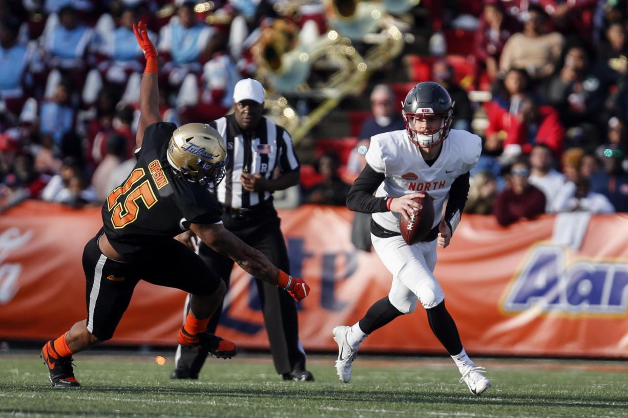 North quarterback Anthony Gordon of Washington State (3) scrambles away from South defensive end Trevis Gipson of Tulsa (15) during the second half of the Senior Bowl college football game Saturday, Jan. 25, 2020, in Mobile, Ala.