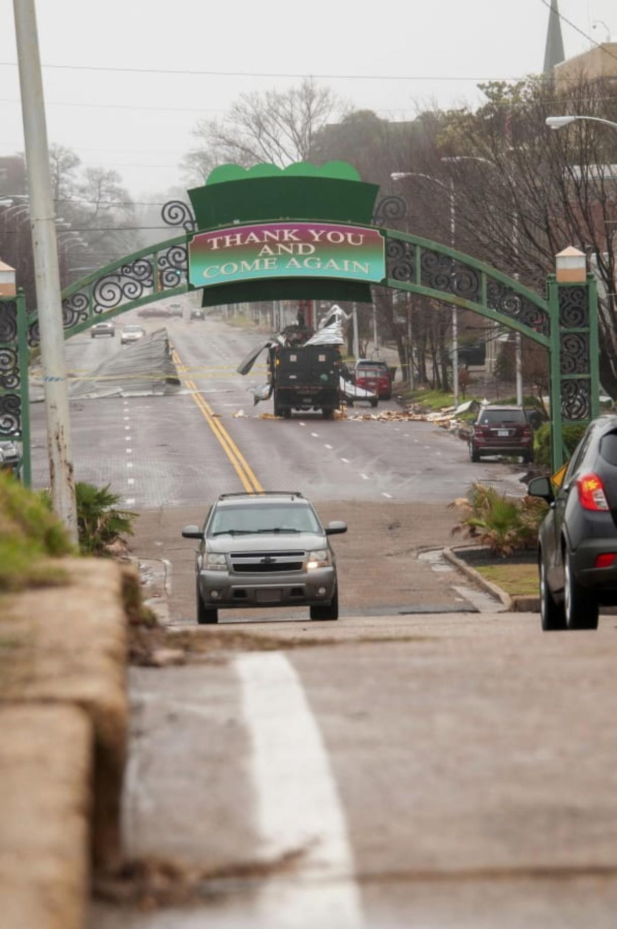 City of Greenville, Miss., trucks and employees, work to clean up debris from a storm along Main Street, Saturday, Jan. 11, 2020, in Greenville, Miss. Severe storms swept across parts of the U.S. South and were blamed for deaths, destruction and damages. (Jon Alverson/The Delta Democrat-Times via AP)