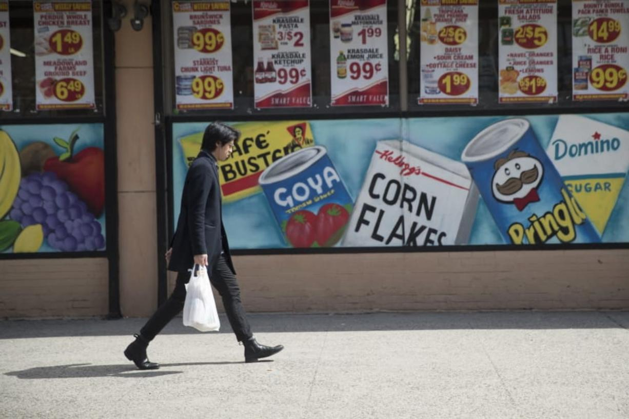 FILE - In this March 27, 2019, file photo a man leaves a supermarket in the East Village neighborhood of Manhattan carrying his groceries in a plastic bag. A growing number of states, counties and cities have passed legislation prohibiting or restricting retailers and other businesses from giving customers single-use plastic bags to carry purchases. Oregon's ban went into effect Jan. 1, 2020 and Maine, New York state and Vermont have similar prohibitions going into effect later in the year.