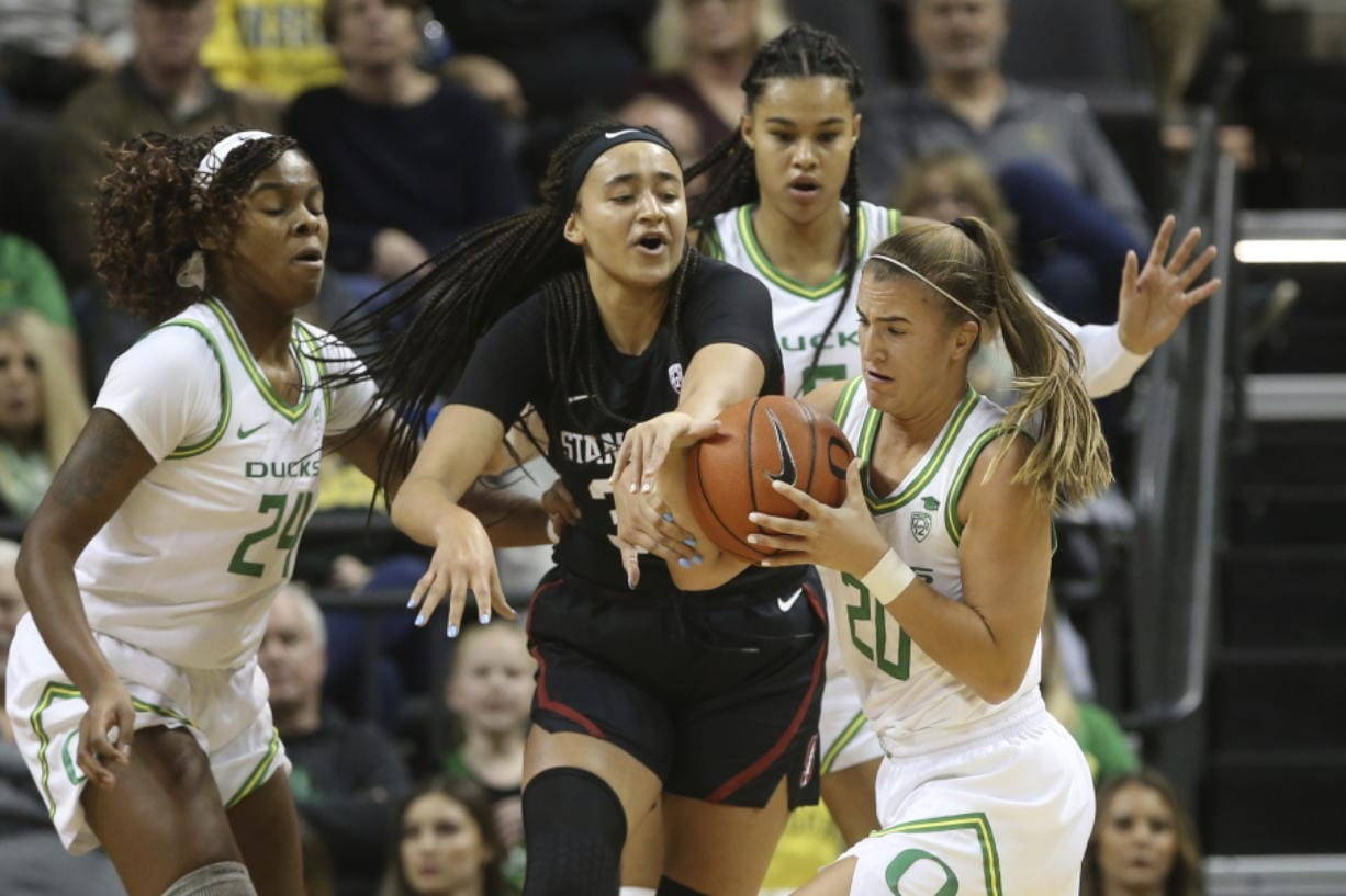 Oregon's Ruthy Hebard, left, Satou Sabally, rear, and Sabrina Ionescu, right, battle Stanford's Haley Jones for the ball during Thursday's game in Eugene, Ore.