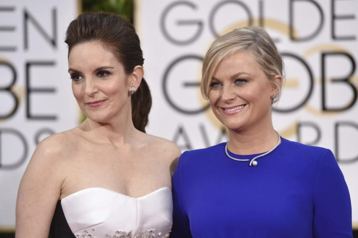 Tina Fey, left, and Amy Poehler arrive for the 72nd annual Golden Globe Awards in Beverly Hills, Calif.