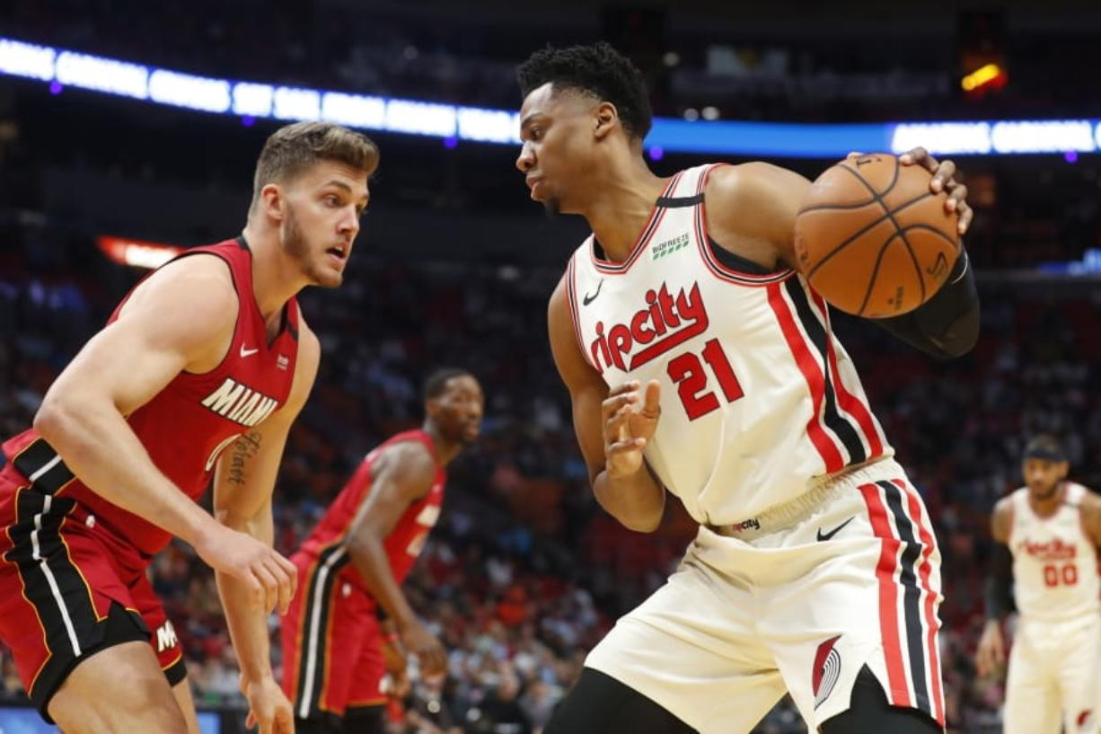 Portland Trail Blazers center Hassan Whiteside (21) drives up against Miami Heat forward Meyers Leonard (0) during the first half of an NBA basketball game, Sunday, Jan. 5, 2020, in Miami. (AP Photo/Wilfredo Lee)