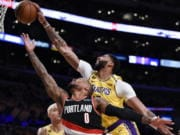 Los Angeles Lakers forward Anthony Davis, top, blocks a shot by Portland Trail Blazers guard Damian Lillard during the first half of an NBA basketball game in Los Angeles, Friday, Jan. 31, 2020.