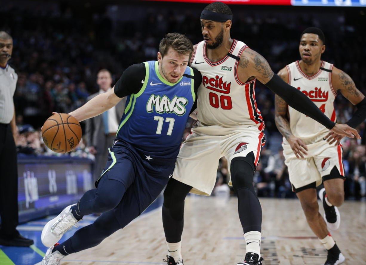 Dallas Mavericks forward Luka Doncic (77) drives on Portland Trail Blazers forward Carmelo Anthony. (Brandon Wade/Associated Press)