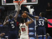 Minnesota Timberwolves' Robert Covington, right, blocks a shot-attempt by Portland Trail Blazers' Hassan Whiteside, center as Timberwolves' Gorgui Dieng, of Senegal, also defends in the first half of an NBA basketball game Thursday, Jan. 9, 2020, in Minneapolis.