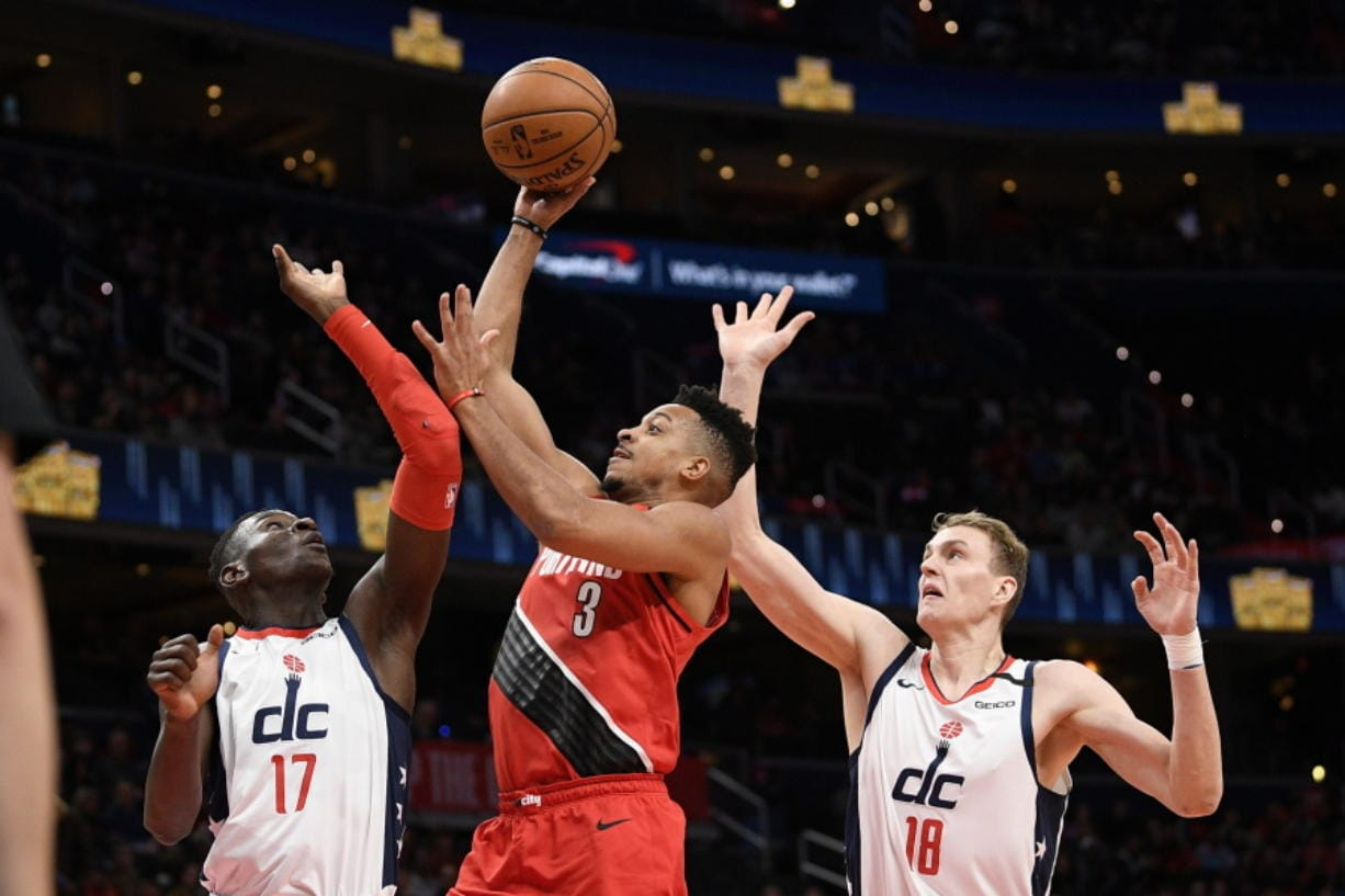 Portland Trail Blazers guard CJ McCollum (3) goes to the basket between Washington Wizards guard Isaac Bonga (17) and center Anzejs Pasecniks (18) during the first half of an NBA basketball game, Friday, Jan. 3, 2020, in Washington. (AP Photo/Nick Wass)