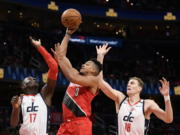 Portland Trail Blazers guard CJ McCollum (3) goes to the basket between Washington Wizards guard Isaac Bonga (17) and center Anzejs Pasecniks (18) during the first half of an NBA basketball game, Friday, Jan. 3, 2020, in Washington.