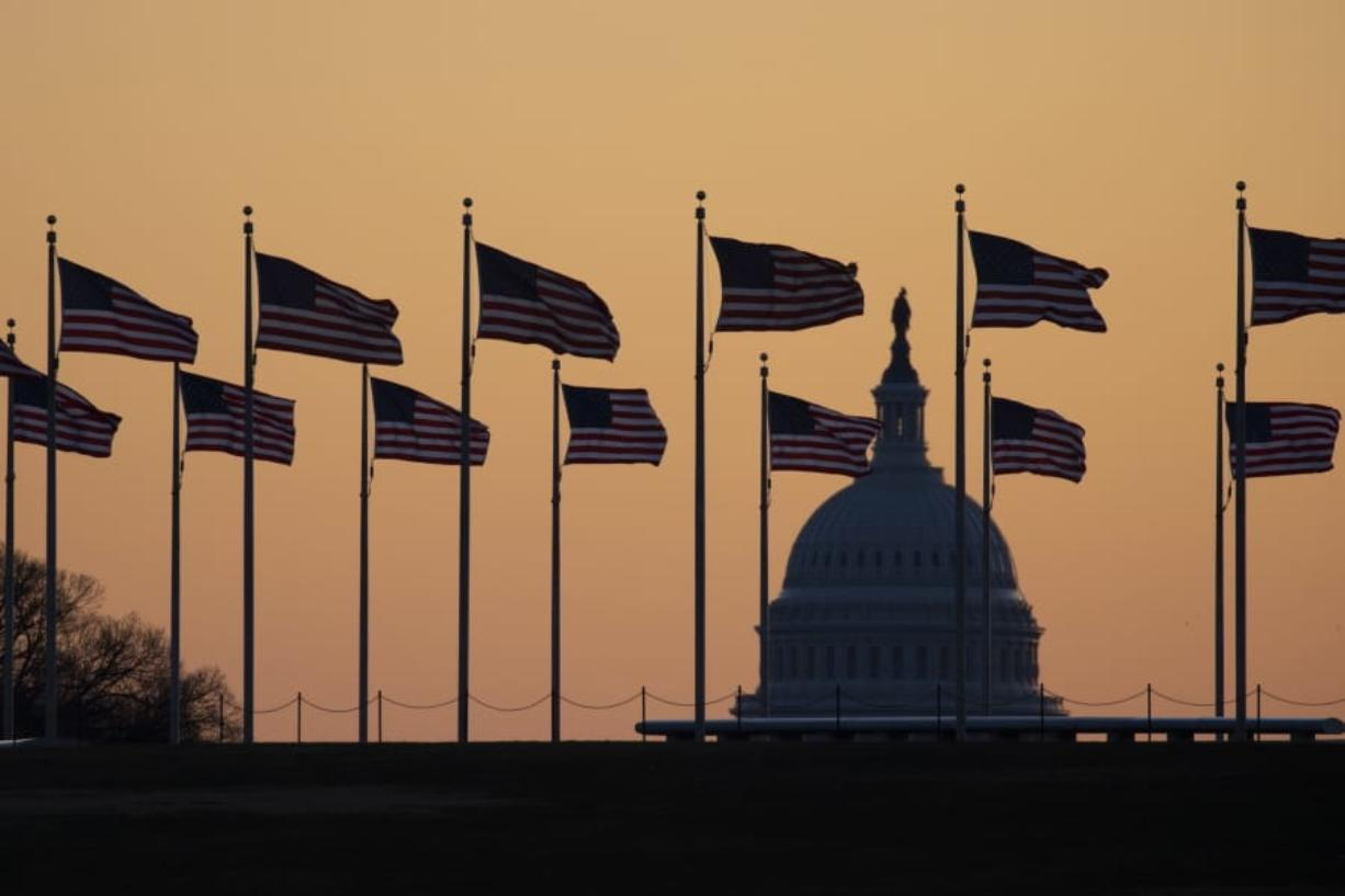 American flags blow in wind around the Washington Monument with the U.S. Capitol in the background at sunrise on Monday, Jan. 20, 2020, in Washington. The impeachment trial of President Donald Trump will resume in the U.S. Senate on Jan. 21.