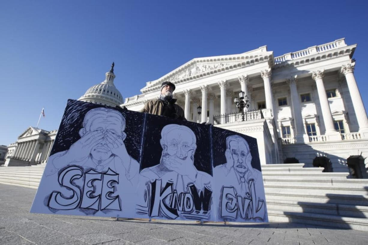 """Stephen Parlato, of Bolder, Colo., displays his artwork depicting, """"the evil Republican senatorial judges"""", as he demonstrates outside the U.S. Capitol Wednesday, Jan. 22, 2020, in Washington."""