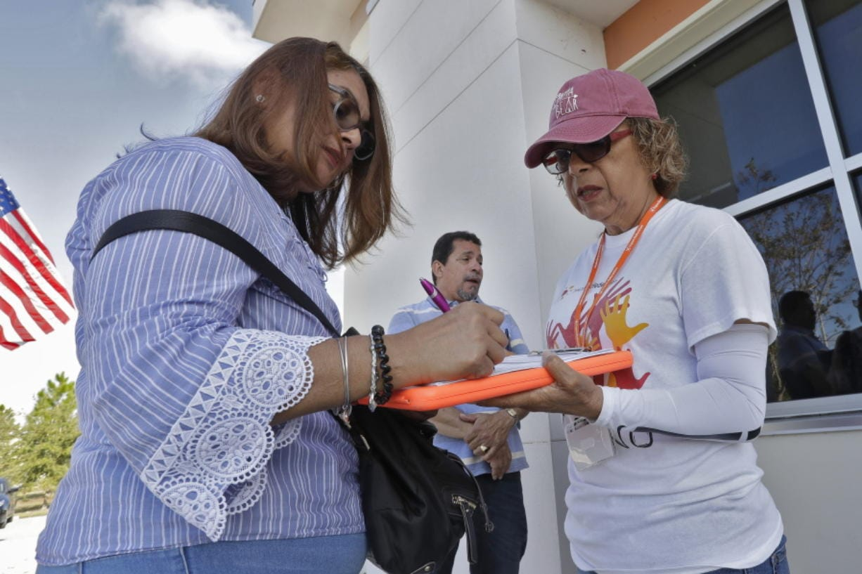 In this Dec. 10, 2019 photo, Hispanic Federation Canvasser Ana M. Vigo, right, registers Maria Moralez, left, to vote as Ivan Baez Munoz looks on outside the Polk Coutny Tax Collectors office in Davenport, Fla.