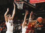 Southern California's Daniel Utomi (4) passes away from the basket to avoid Oregon State's Kylor Kelley (24) and Tres Tinkle (3) during the first half of an NCAA college basketball game in Corvallis, Ore., Saturday, Jan. 25, 2020.