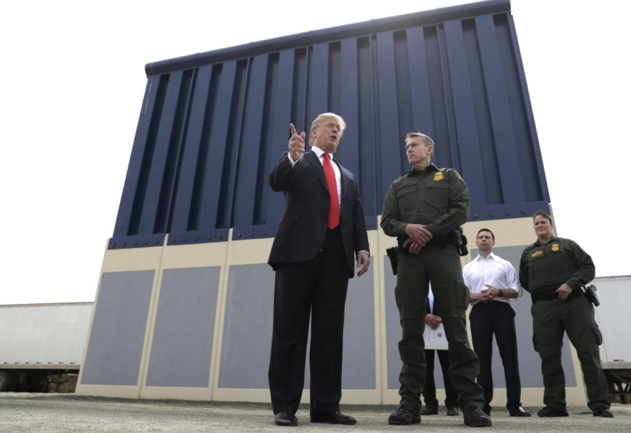 FILE - In this March 13, 2018, file photo, President Donald Trump speaks during as he reviews border wall prototypes, in San Diego, as Rodney Scott, the Border Patrol's San Diego sector chief, listens. The Trump administration has named Rodney Scott the new head of the U.S. Border Patrol. Scott will take over for Carla Provost, who is retiring, according to an announcement obtained Friday by The Associated Press from Mark Morgan, acting head of U.S. Customs and Border Protection. Scott has been a member of the Border Patrol for 27 years.