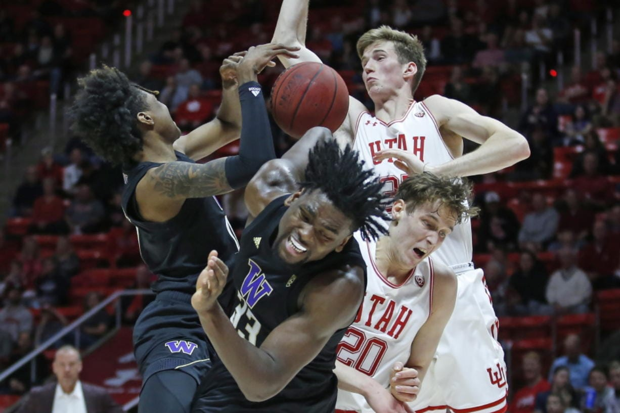 Washington's Jaden McDaniels, left, and Isaiah Stewart (33) battle against Utah's Mikael Jantunen (20)and Branden Carlson, rear, for a rebound in the first half during an NCAA college basketball game Thursday, Jan. 23, 2020, in Salt Lake City. (AP Photo/Rick Bowmer)