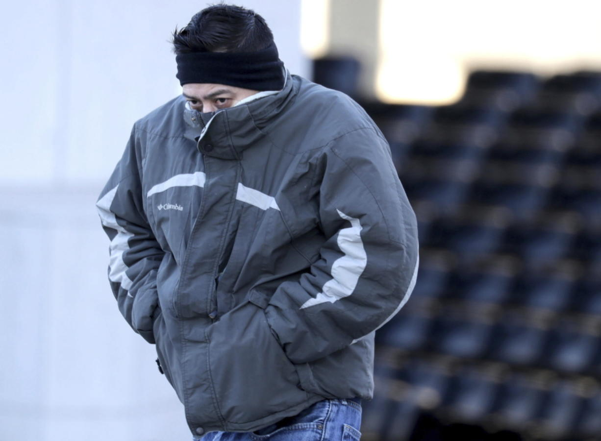 Jorge Hernandez, of Milwaukee, tries to cover his face from the cold while walking along West Kilbourn Avenue in Milwaukee, Thursday, Jan. 16, 2020. While snow is expected Friday, breezy and cold conditions return on Sunday and Monday, with wind chills of minus 10 to minus 15 Fahrenheit across the region, according to the National Weather Service office in Sullivan. (Mike De Sisti/Milwaukee Journal-Sentinel via AP)