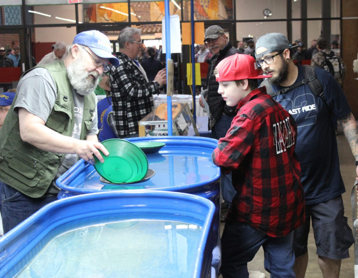 Zachary Castillo, center, watches a demonstration on panning gold as his father looks on. The Pacific Northwest Sportsmen's Show at the Portland Expo Center in Portland opened on Wednesday and will run through Sunday. (Terry Otto/The Columbian)