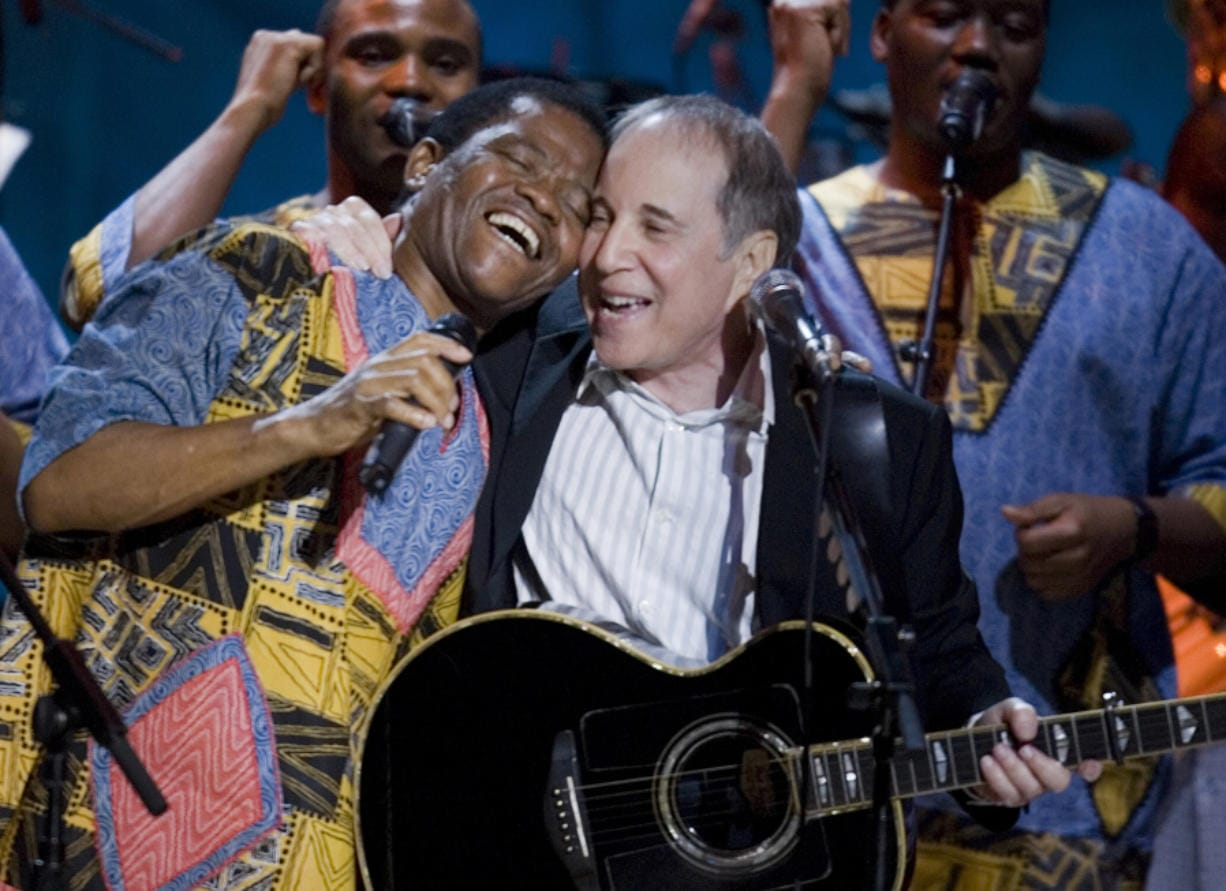 Paul Simon, center, Joseph Shabalala, left, and other members of Ladysmith Black Mambazo perform during the Library Of Congress Gershwin Prize For Popular Song Gala at the Warner Theater May 23, 2007, in Washington, D.C. Shabalala has died at age 78. (Brendan Smialowski/Getty Images)