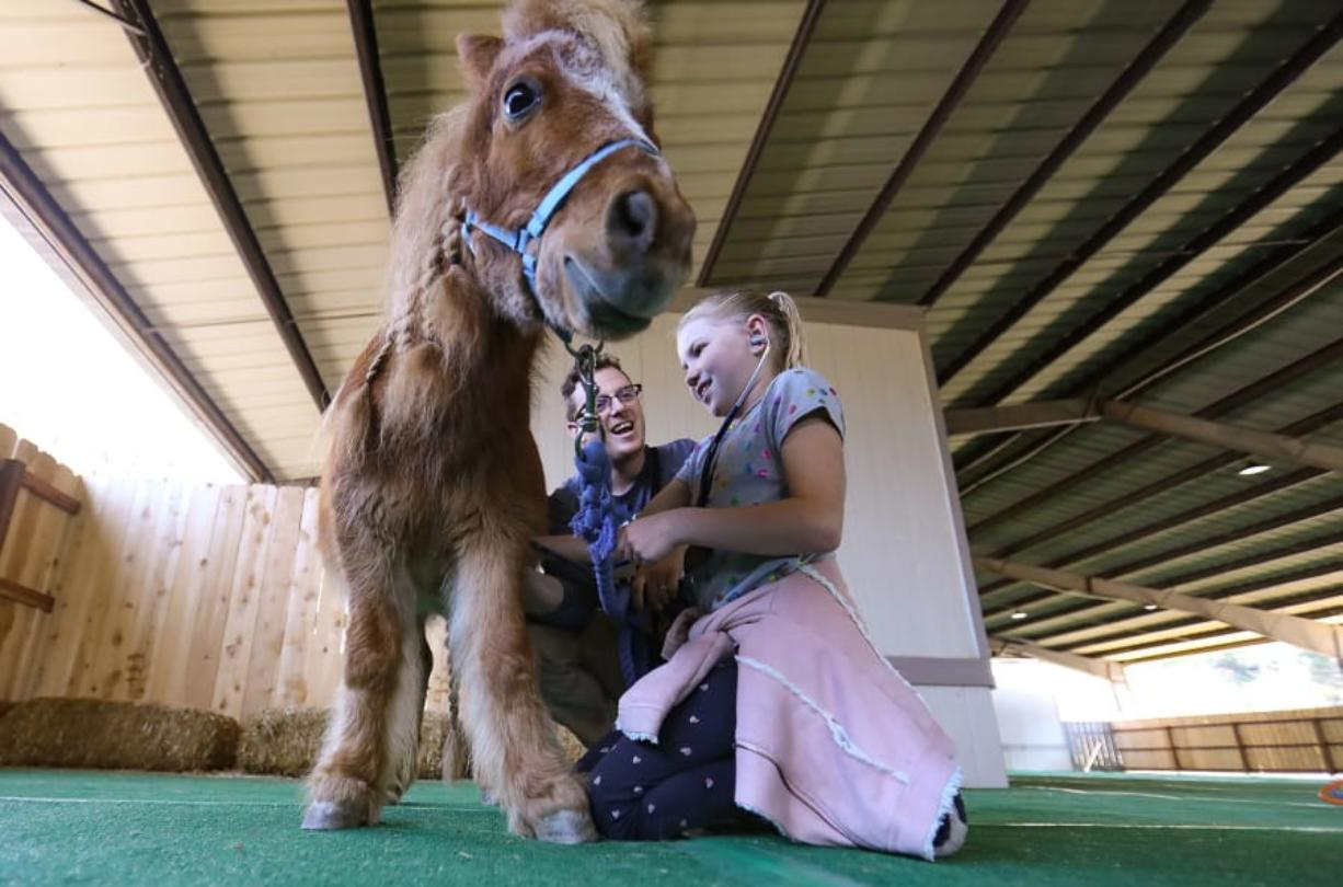 Kaylee Taylor, 9, a fourth-grader, uses a  stethoscope to listen to the heart of Fable, a miniature horse, with the help of Justin Norris, education coordinator at the Helen Woodward Animal Center, during the one-day veterinarian camp at the center Saturday in Rancho Santa Fe, Calif. (Howard Lipin/San Diego Union-Tribune)