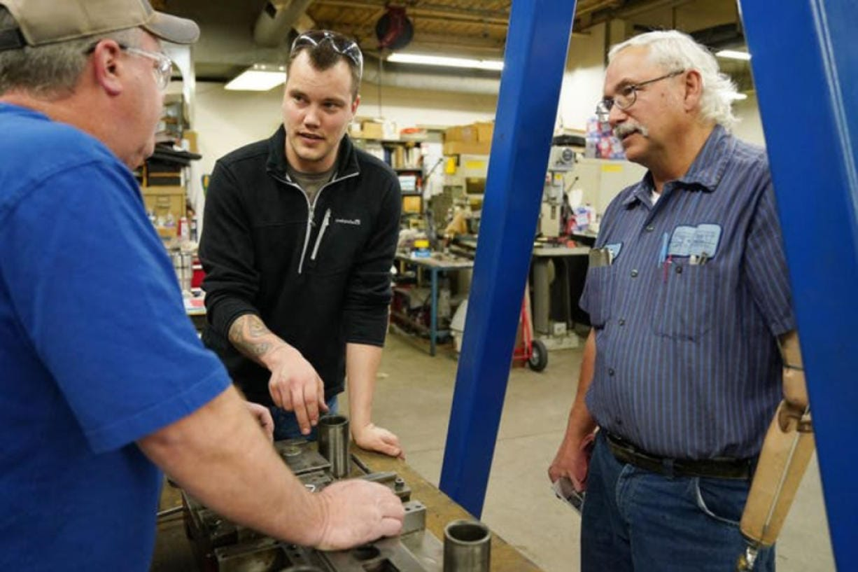 Justin Vandevoort, center, talked with machinist Rod Sammon, left, and press department lead Ben Froman as they worked with a metal stamping die at MRG Tool & Die in Faribault, Minn.