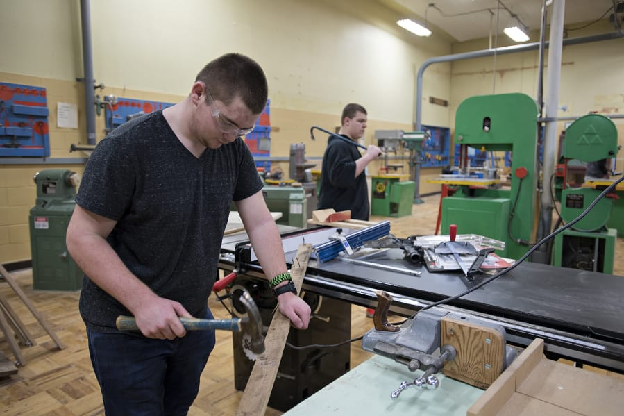 Ridgefield High School sophomore Tynan Henderson, 16, removes nails from boards while working during wood tech class in February 2020 — not long before students went to remote schooling.