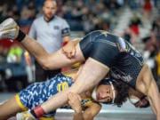 Seton Catholic junior Elijah Volk, bottom, takes down Royal's Kaleb Hernandez in a Class 1A 145-pound quarterfinal on Friday at Mat Classic XXXII in the Tacoma Dome. Volk won by 8-4 decision.
