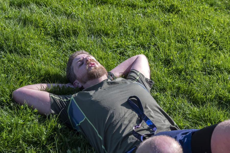 Zack Freeman of Tigard, Ore.,lies down in the grass after completing the Vancouver Lake Half Marathon.