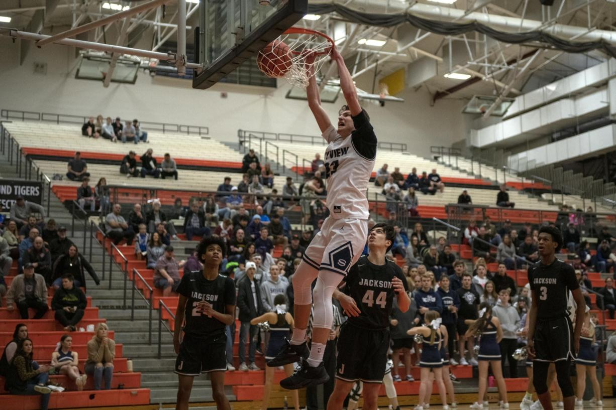 Skyview's Kyle Gruhler (23) hangs on the rim after finishing.a dunk at Battle Ground High School on Saturday evening, Feb. 29, 2020.