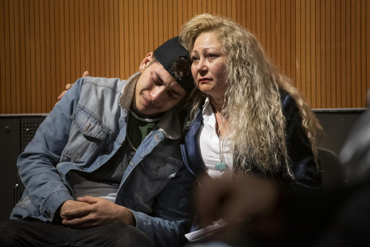 "Lennes Flores, left, cries while hugging his mother, Enedis Flores, after watching a documentary that tells their family's story during The Columbian's ""Bridging the Border"" forum at the Vancouver Community Library on Thursday."