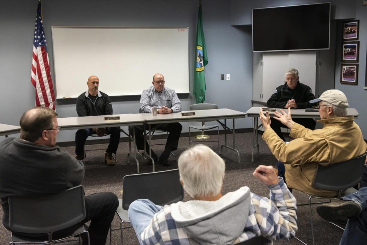 Clark County Fire District 3 Commissioners Rick Steele, center left, and Scott Anders, center right, listen to residents during an informational meeting about annexation Tuesday night at Station 31 in Brush Prairie. (Nathan Howard/The Columbian)