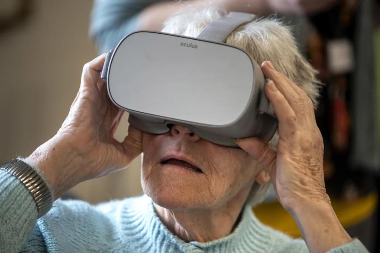 Bonaventure of Vancouver resident Patricia Hulslander tries out a photographic tour of Paris's Notre-Dame Cathedral with a virtual reality headset at the retirement community in Vancouver. Fort Vancouver Regional Libraries worked with Bonaventure of Vancouver to provide residents with the virtual vacation activity.